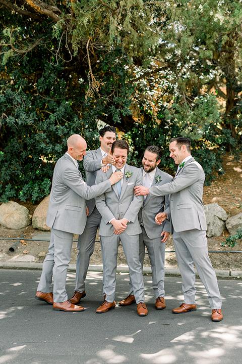 Temecula-Creek-Inn-Wedding-groomsmen-and-groom-in-a-light-grey-suit-with-blue-patterned-ties