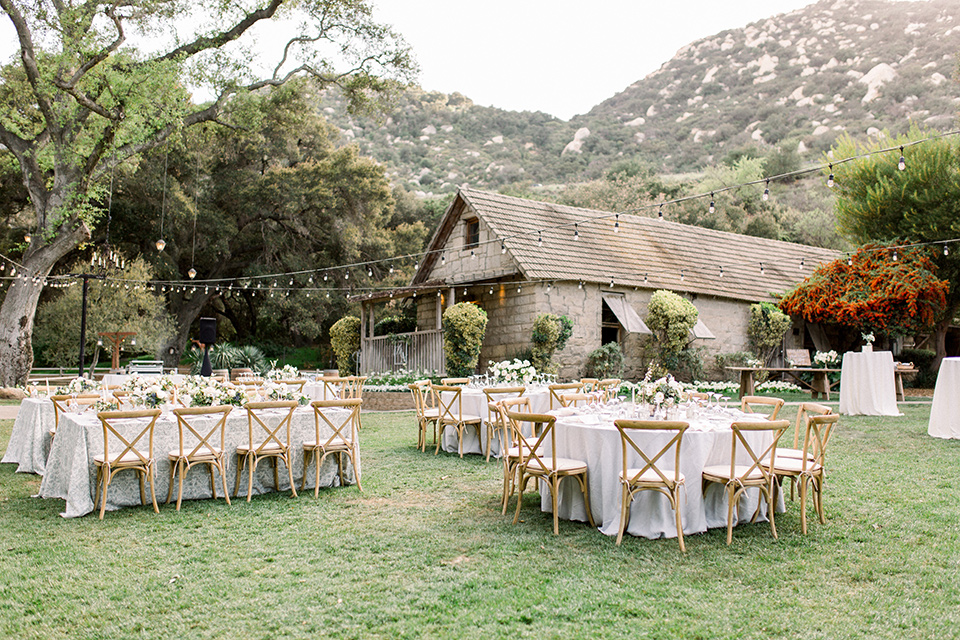 Temecula-Creek-Inn-Wedding-reception-area-with-wooden-tables-and-chairs-with-string-lights