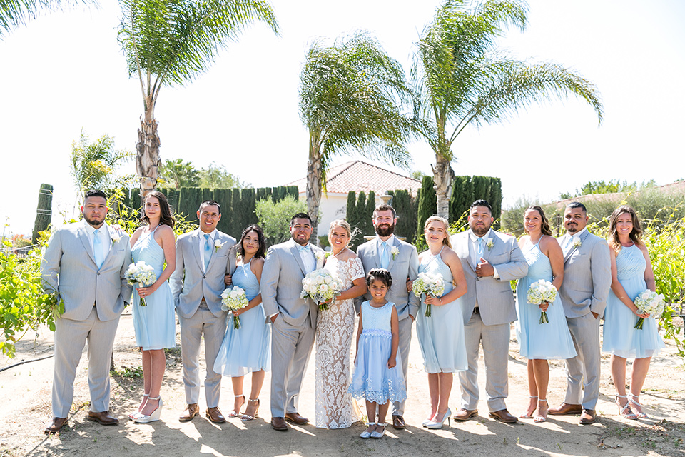 bride in a lace formfitting gown with an illusion neckline the groom in a light grey suit and bow tie, the groomsmen in light grey suits and blue ties and the brides maids in light blue short gowns