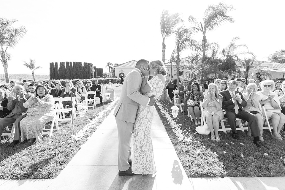 bride in a lace formfitting gown with an illusion neckline the groom in a light grey suit and bow tie