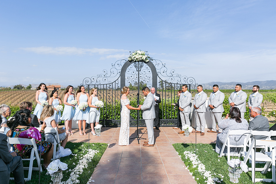 bride in a lace formfitting gown with an illusion neckline the bridesmaids in light blue short gowns groomsmen in light grey suits and groom in a light grey suit