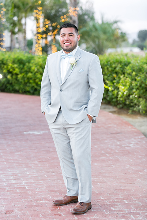 the groom in a light grey suit and bow tie