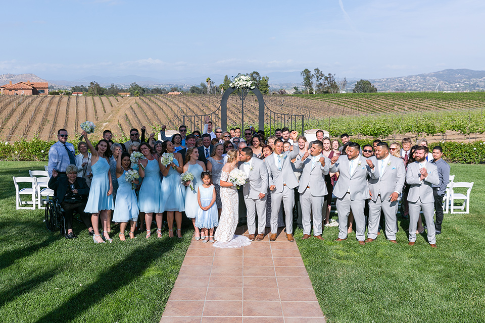 groom and groomsmen in a light grey suit and bow tie and light blue long ties bridesmaids in light blue suits and all the guests smiling