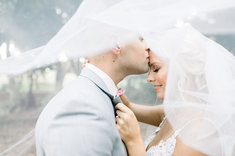 bride and groom pose under veil