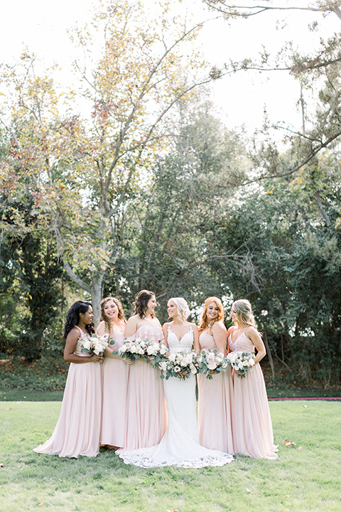 Bridesmaids and bride in pink dresses posing for a picture