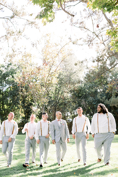 Groom and Groomsmen posing for a picture in suspenders