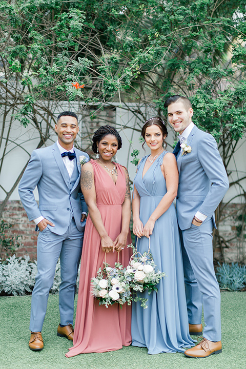bridesmaids in a coral gown + light blue gown and the groomsmen in a light blue suit