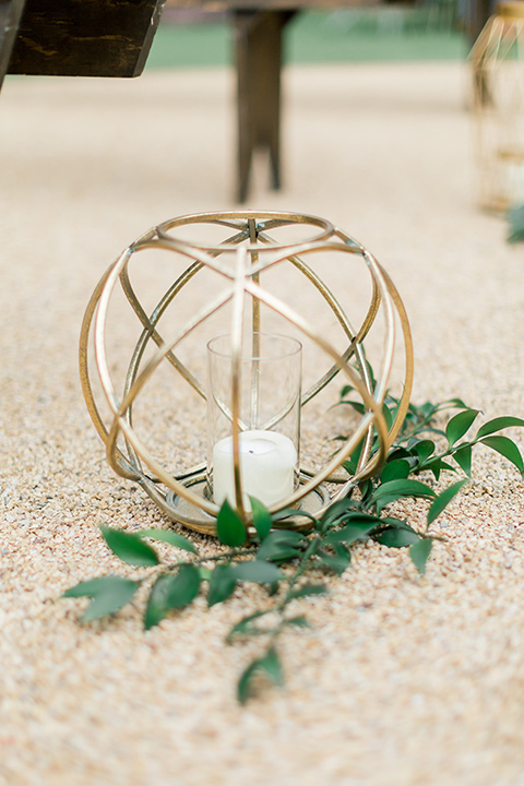 gold wire décor with white candles lining the ceremony aisle