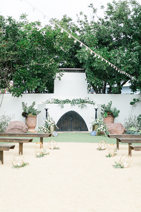 white ceremony space with string lights and long picnic seats