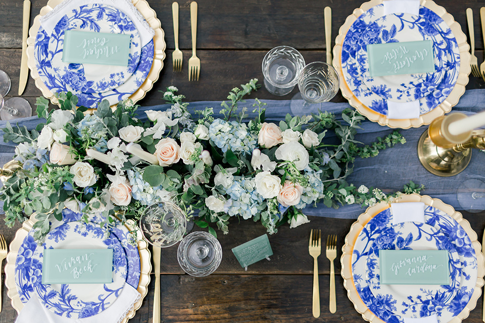 white and blue floral design on plates and gold flatware