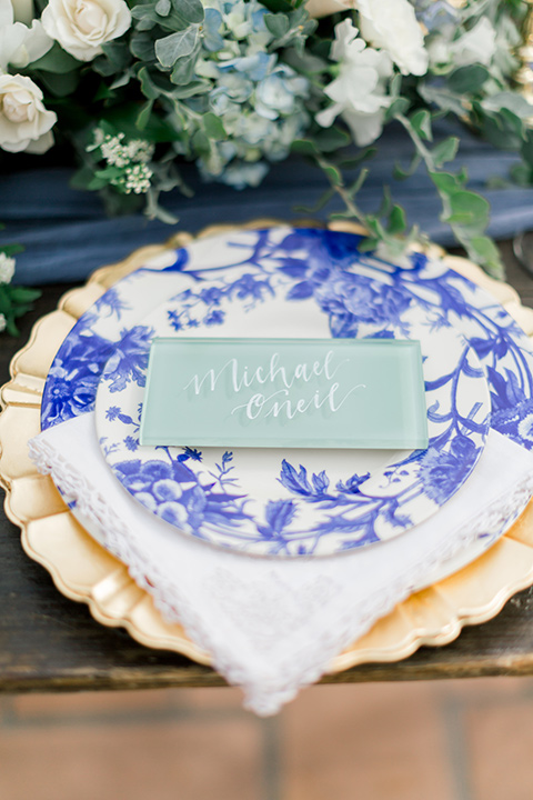 white and blue floral design on the plates and gold décor and flatware