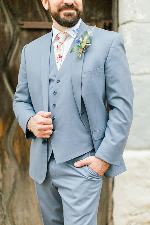 groom in light blue suit and white floral neck tie