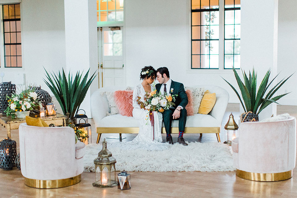 modern Moroccan shoot bride and groom on the couch at the reception the bride in a white lace gown with long sleeves and a v neck line and the groom is in a green suit with a brown long tie