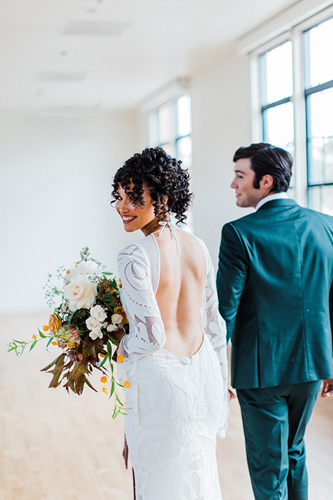 modern Moroccan shoot bride and groom walking by the windows the bride in a white lace gown with long sleeves and a v neck line and the groom is in a green suit with a brown long tie