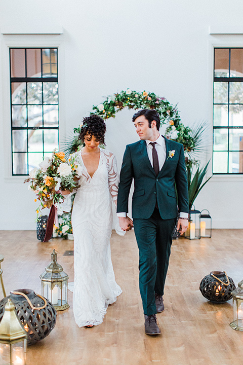 modern Moroccan shoot bride and groom at ceremony space walking down the aisle the bride in a white lace gown with long sleeves and a v neck line and the groom is in a green suit with a brown long tie