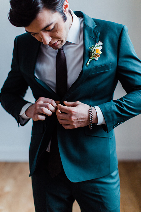 modern Moroccan shoot groom buttoning his jacket in a green suit with a brown long tie