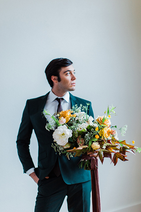 modern Moroccan shoot groom holding flowers in a green suit with a brown long tie