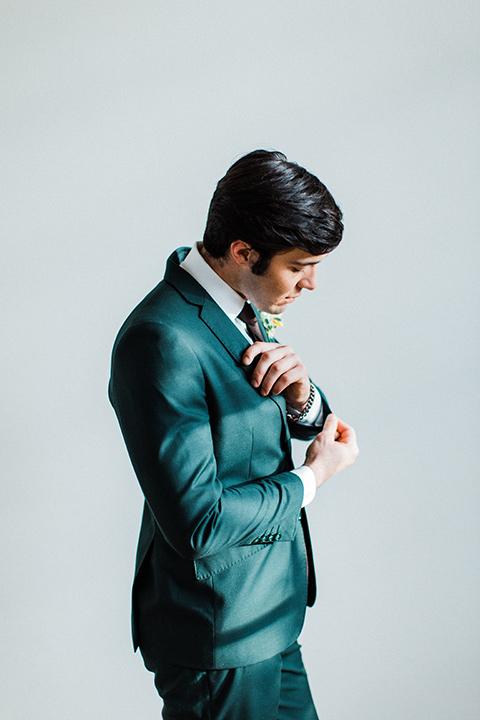 modern Moroccan shoot groom fixing sleeves in a green suit with a brown long tie