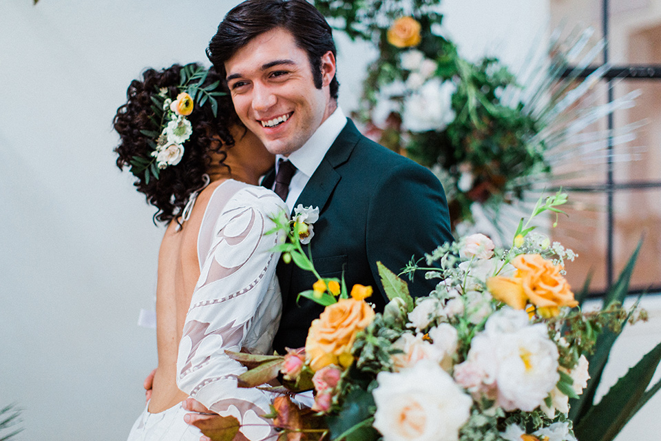 modern Moroccan shoot bride and groom touching smiling the bride in a white lace gown with long sleeves and a v neck line and the groom is in a green suit with a brown long tie