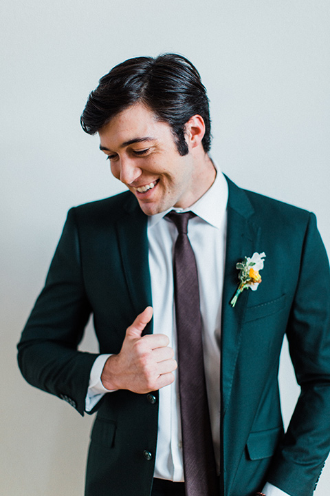 modern Moroccan shoot groom smiling in a green suit with a brown long tie
