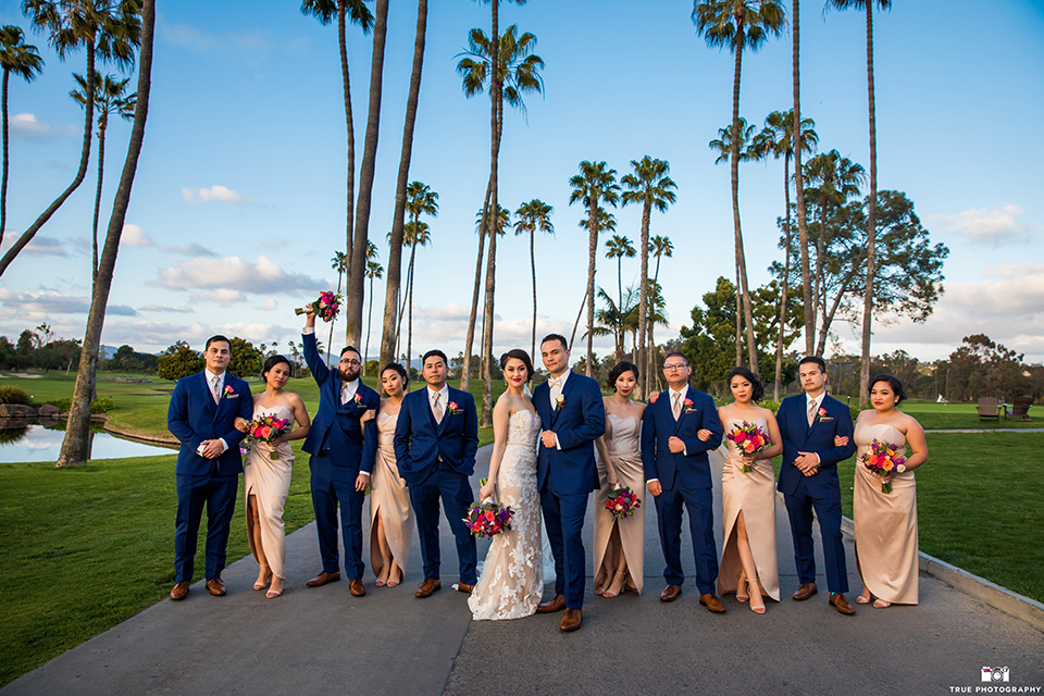 bride in a white lace strapless gown and groom in a blue suits and groomsmen in blue suits and bridesmaids in champagne gowns