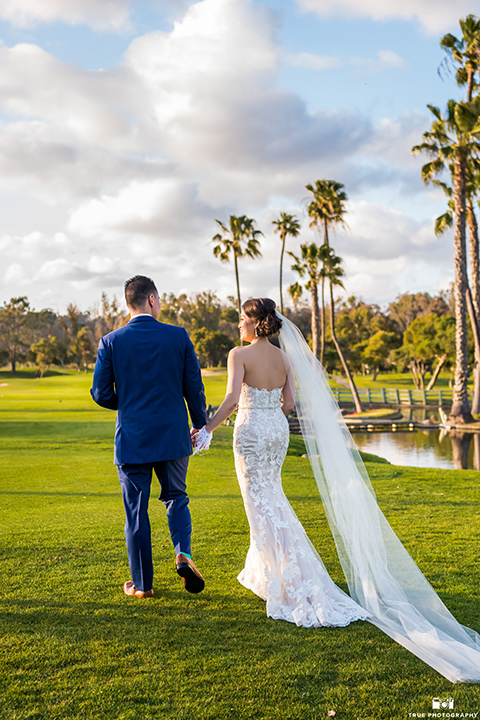 bride in a white gown with a lace strapless neckline and the groom in a blue suit