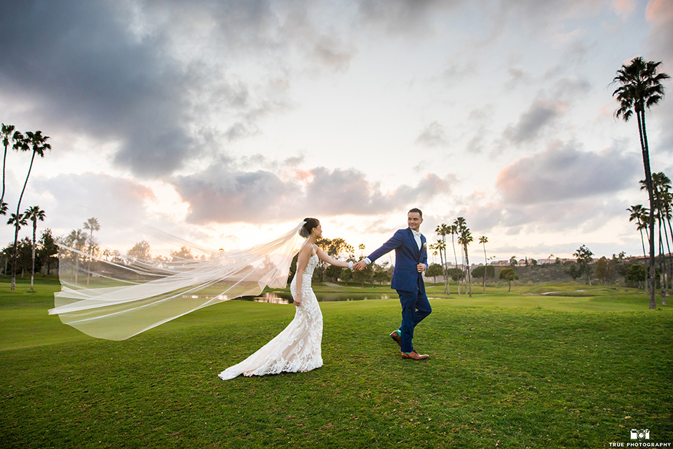 bride in a white lace strapless gown and groom in a blue suits