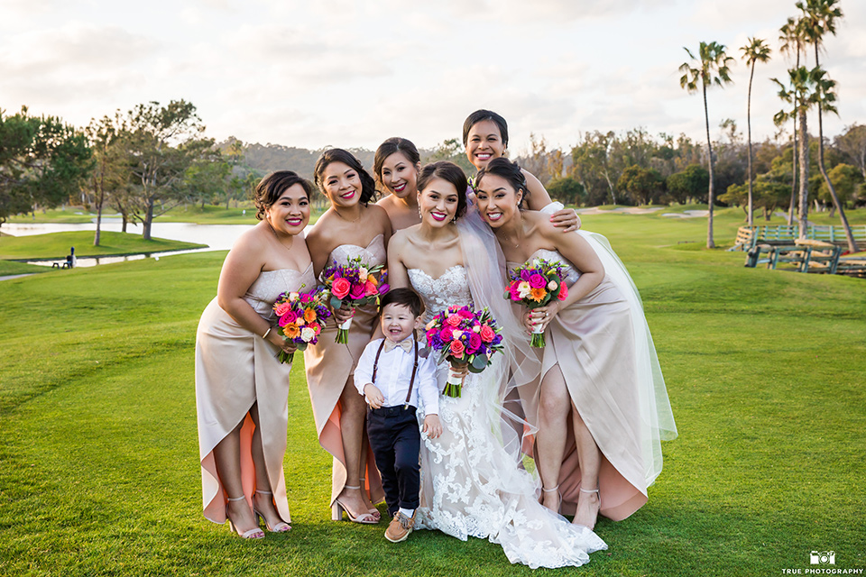 bride in a white lace strapless gown and bridesmaids in champagne colors gowns