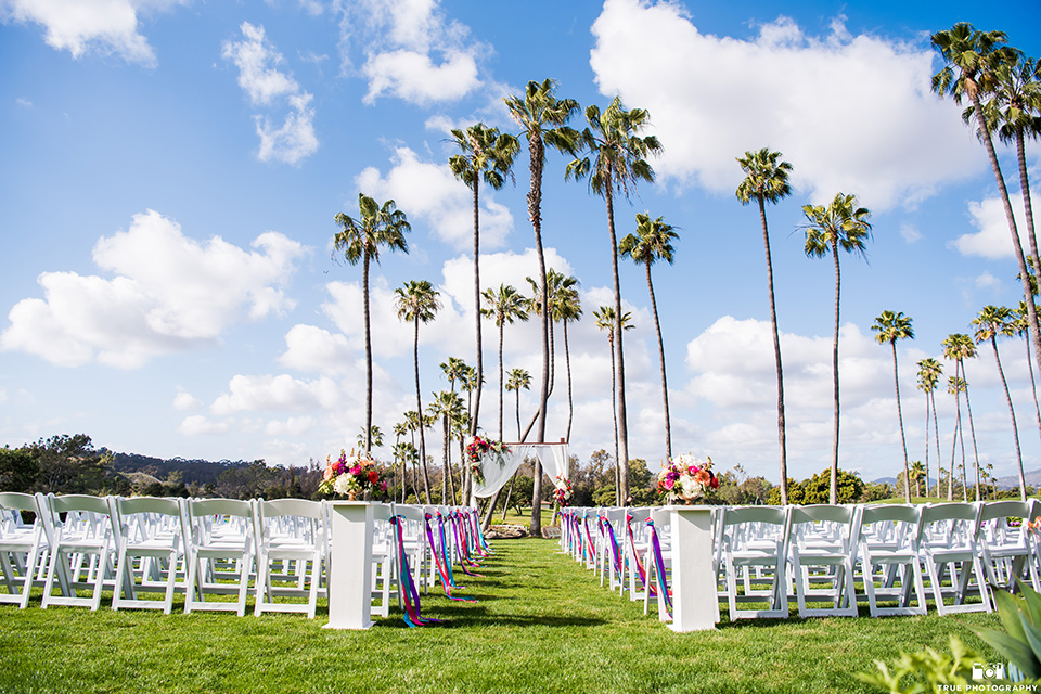 white chairs and colorful floral and ribbon accents