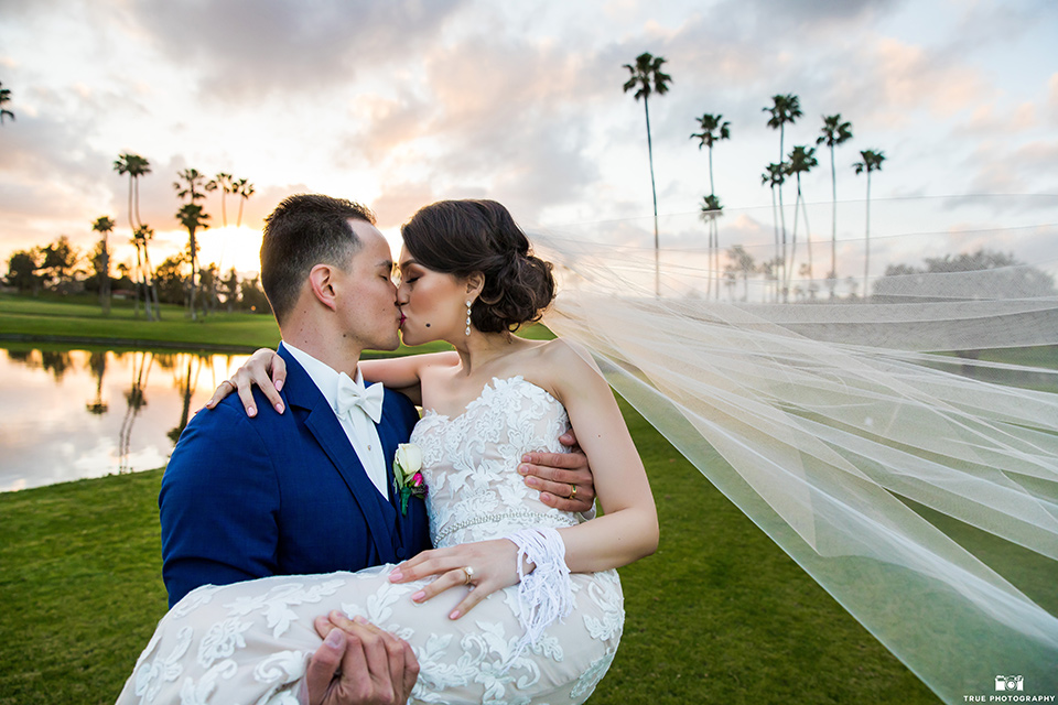 bride in a white lace strapless gown and groom in a blue suit and bow tie