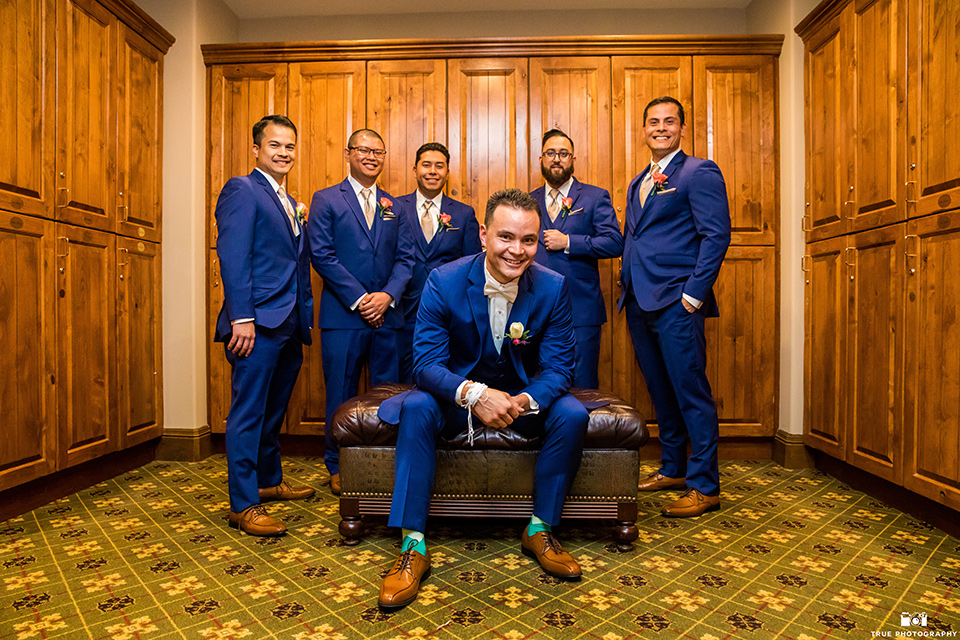 groom and groomsmen in blue suits and bow ties