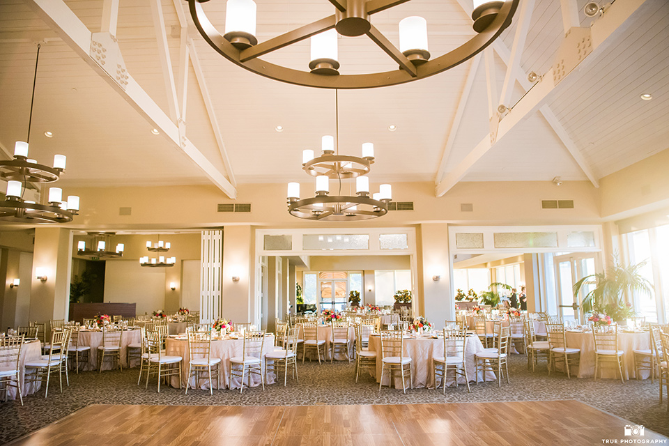 indoor reception space with white linens and hanging chandeliers
