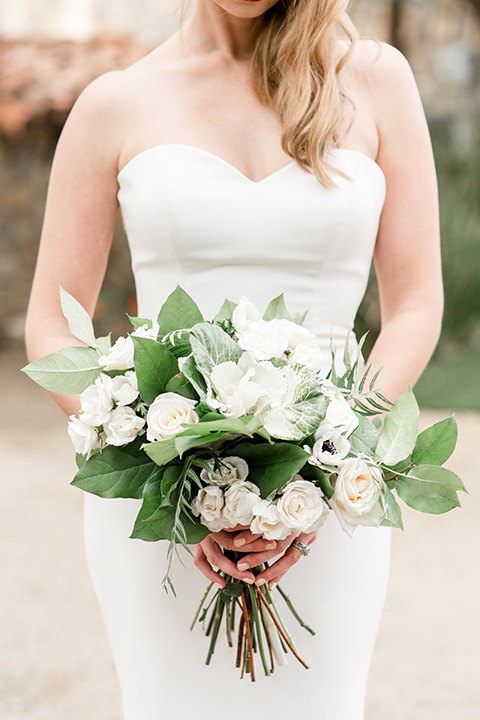 Bride posing in a strapless dress and holding a bouquet of flowers