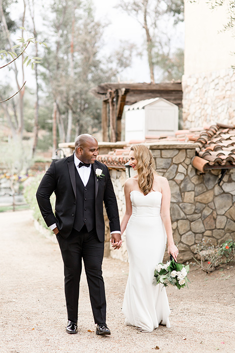 Oak-Meadows-Shoot-bride-and-groom-walking-by-venue-bride-wearing-a-lace-strapless-dress-groom-in-a-black-notch-lapel-tuxedo-with-a-black-bow-tie