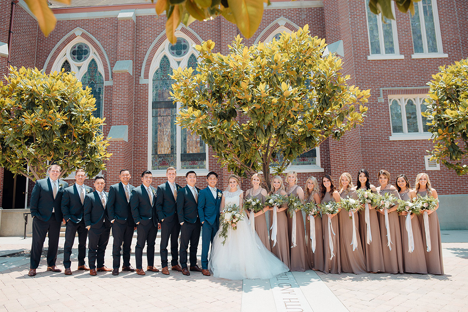 orange-county-wedding-bridal-party-outside-church-bridesmaids-in-a-taupe-dress-color-bride-in-a-two-piece-lace-ballgown-groomsmen-in-a-dark-navy-suit-groom-in-a-brighter-blue-suit-with-a-flowal-bowtie