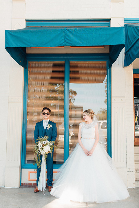 orange-county-wedding-bride-and-groom-under-blue-window-awning.jpg