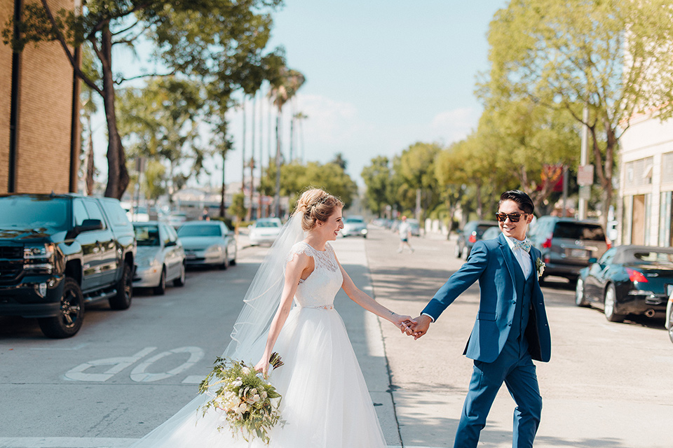 orange-county-wedding-bride-and-groom-walking-across-the-street-bride-in-a-two-piece-lace-ballgown-groom-in-a-brighter-blue-suit-with-a-flowal-bowtie