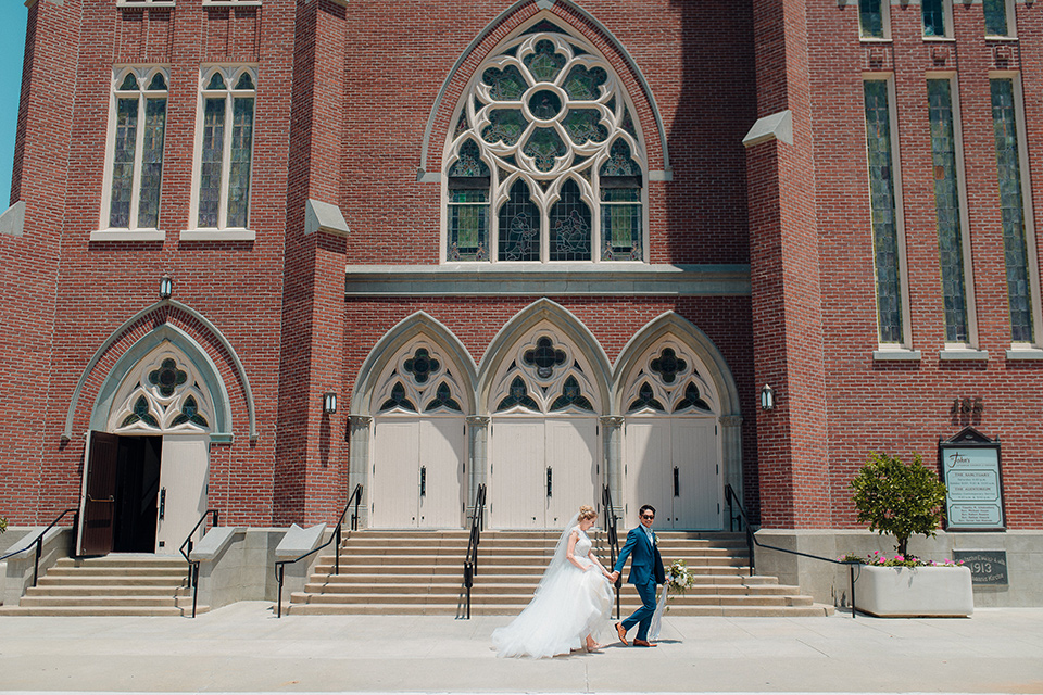 orange-county-wedding-bride-and-groom-walking-in-front-of-church-bride-in-a-two-piece-lace-ballgown-groom-in-a-brighter-blue-suit-with-a-flowal-bowtie
