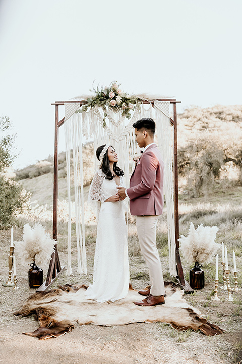 Owl-Creek-Farms-shoot-bride-and-groom-at-ceremony-bride-wearing-a-bohemian-style-dress-with-flutter-sleeves-and-a-macrame-style-headpiece-groom-in-a-rose-pink-suit-jacket-with-tan-pants-and-a-velvet-bow-tie