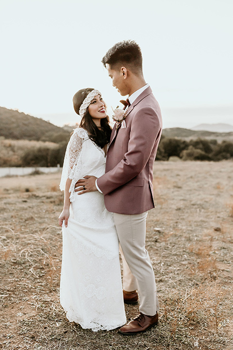 Owl-Creek-Farms-shoot-bride-and-groom-laughing-at-ceremony-bide-in-a-flowing-boho-gown-with-sleeves-groom-in-a-rose-pink-suit-and-velvet-bowtie