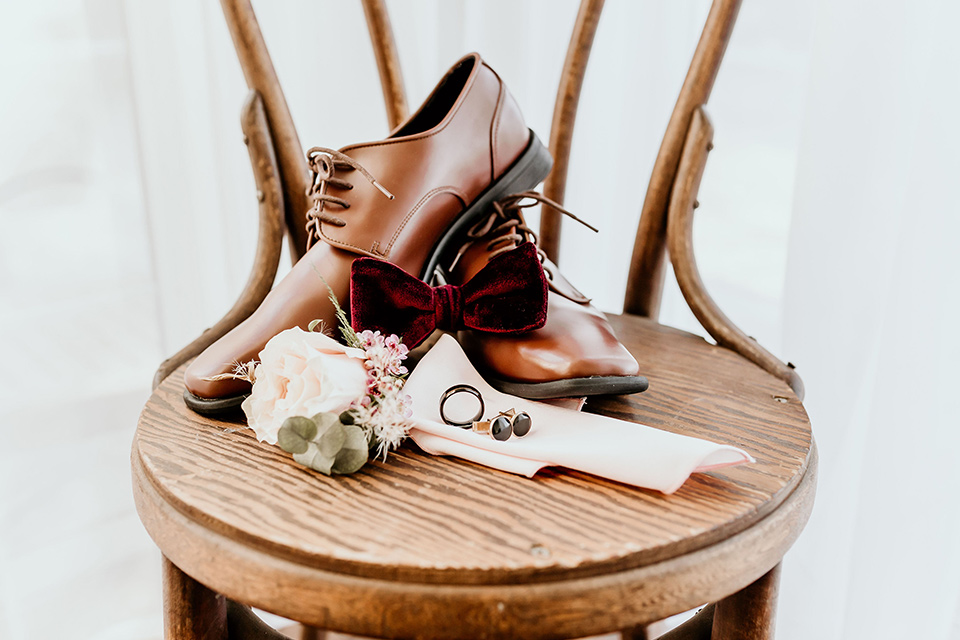 Owl-Creek-Farms-shoot-groom-accessories-on-chair-with-brown-shoes-burgundy-velvet-bow-tie-studs-and-cufflinks
