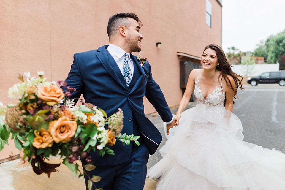 groom in a deep blue suit and floral tie running with bride in a white tulle ballgown