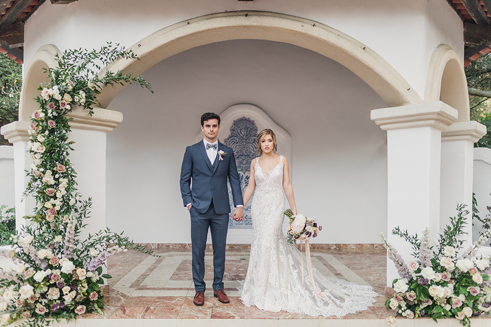 bride-and-groom-standing-facing-camera-while-the-bride-is-wearing-a-lace-dress-with-straps-and-illusion-back-groom-in-a-dark-blue-suit-with-a-grey-velvet-bow-tie