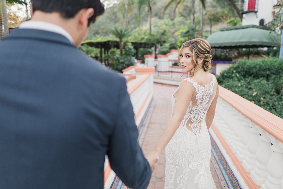 rancho-las-lomas-wedding-bride-taking-grooms-hand-bride-is-wearing-a-lace-dress-with-straps-and-illusion-back-groom-in-a-dark-blue-suit-with-a-grey-velvet-bow-tie