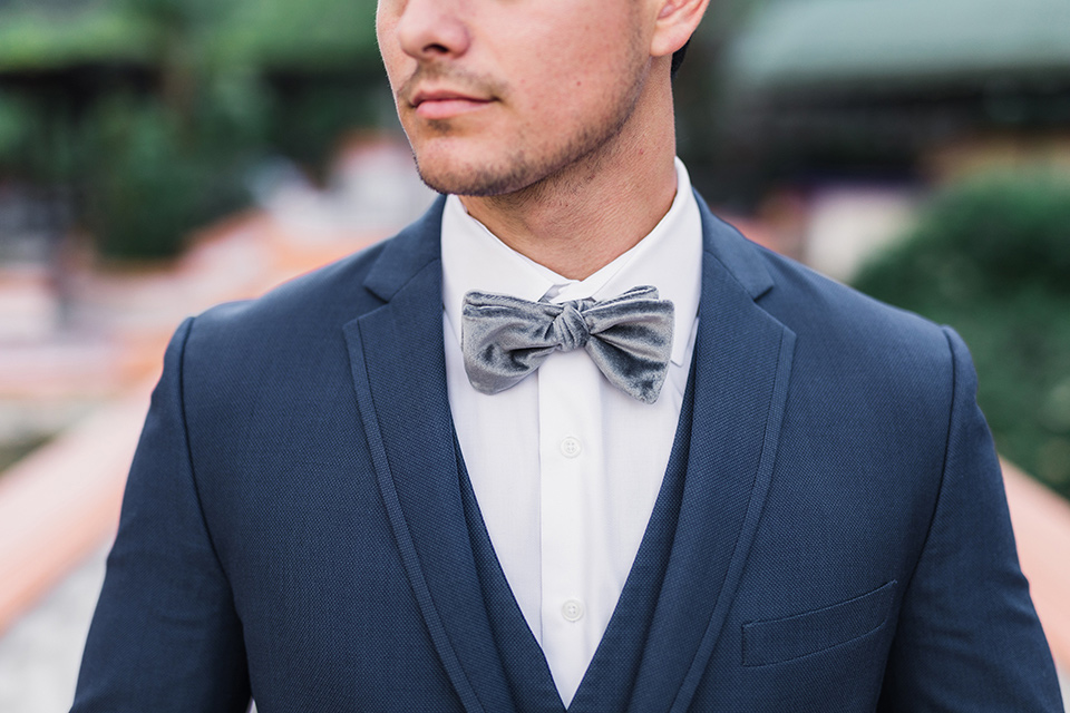 rancho-las-lomas-wedding-close-up-on-groom-attire-groom-in-a-dark-blue-suit-with-a-grey-velvet-bow-tie