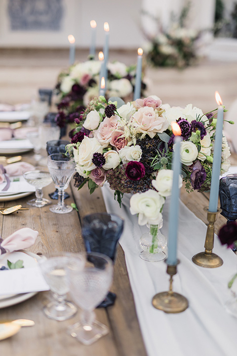 rancho-las-lomas-wedding-close-up-on-table-décor-with-blue-candles-and-purple-flowers