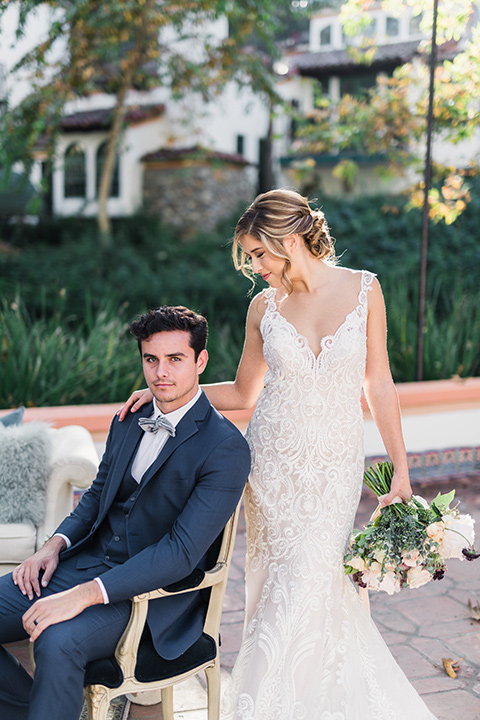 rancho-las-lomas-wedding-groom-sitting-bride-standing-looking-down-at-him-bride-in-lace-with-dress-groom-in-blue-suit-with-grey-bowtie