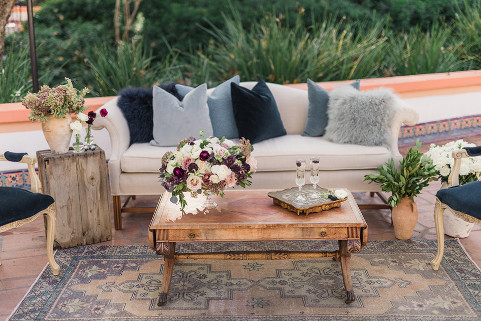 rancho-las-lomas-wedding-outdoor-furniture-décor-with-purple-accented-pillows-and-wooden-tables