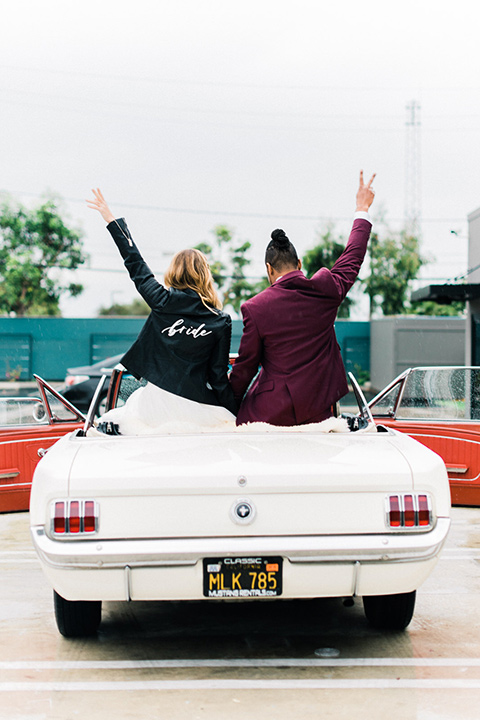 rock-n-roll-wedding-style-bride-and-groom-in-car-bride-in-a-white-flowing-gown-and-a-black-leather-jacket-groom-in-a-deep-burgundy-suit-with-floral-bow-tie