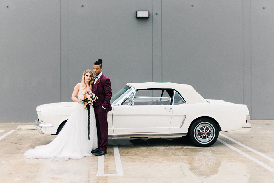 rock-n-roll-wedding-style-bride-and-groom-in-front-of-car-bride-in-a-white-flowing-gown-and-a-black-leather-jacket-groom-in-a-deep-burgundy-suit-with-floral-bow-tie